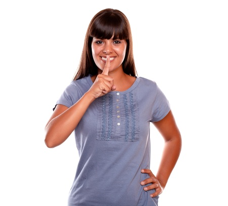 requesting: Charming young woman requesting silence on blue shirt against white background Stock Photo