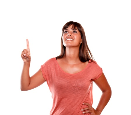 Smiling young woman pointing and looking up on isolated background - copyspace photo
