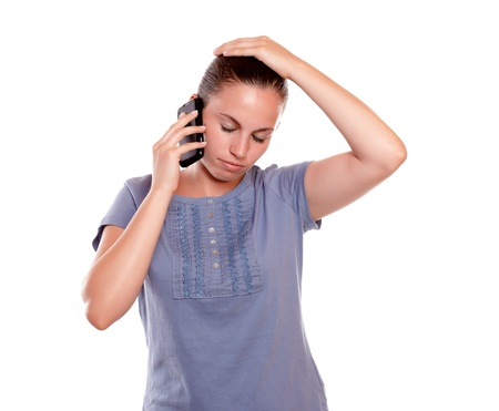 conversing: Stressed young woman conversing on cellphone standing over white background