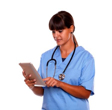nurse uniform: Retrato de una enfermera profesional joven que usa su tableta en uniforme azul con un estetoscopio en el fondo aislado