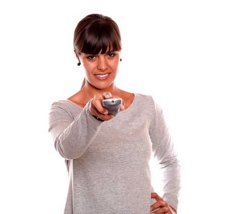Portrait of a smiling young woman using a tv remote against white background photo