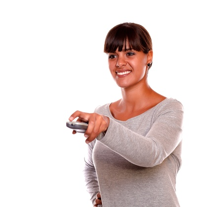Portrait of a smiling young female using a tv remote against white background photo