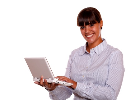 Portrait of a young woman looking at you using her laptop computer against white background photo