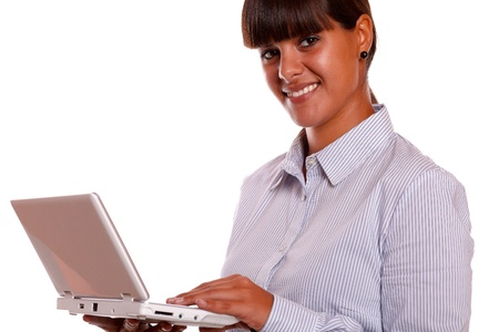 Portrait of a young female looking at you using her laptop computer against white background photo