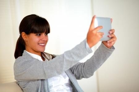 Smiling young woman taking a picture with tablet pc to herself at home indoor photo