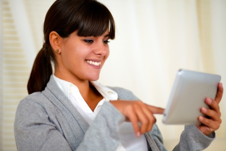 Portrait of a smiling young woman reading a text on tablet pc screen at soft colors composition photo
