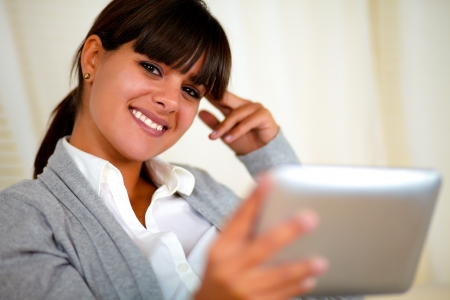 Portrait of a smiling young woman looking at you and reading on tablet pc screen photo