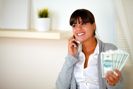 Portrait of a pretty young woman looking at her right and speaking on cellphone with money photo