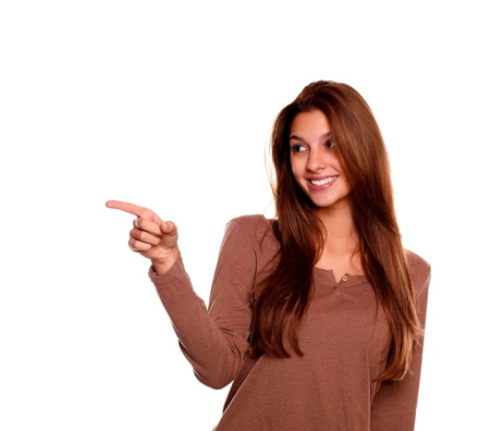 Portrait of a smiling young woman pointing and looking to her right with long brown hair on isolated background - copyspace Stock Photo - 17184729