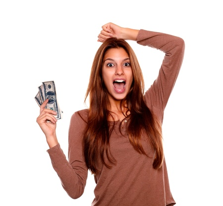 Portrait of a young woman celebrating and holding cash money on brown t-shirt against white background photo
