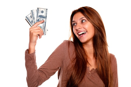 Portrait of a smiling and happy young female holding up cash money with long brown hair on white background