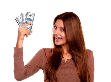 Portrait of a charming young female with cash money with long brow hair against white background photo