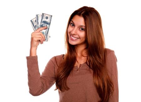 mano con dinero: Retrato de una mujer joven encantadora y sonriente con el dinero en efectivo contra el fondo blanco