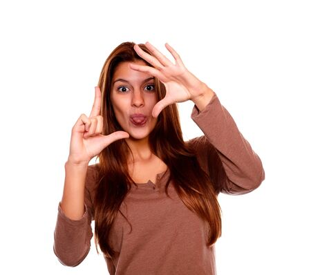 the stinking: Portrait of a young woman sticking out her tongue making a frame with her hands and looking at you against white background