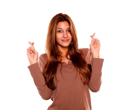 crossing fingers: Portrait of a friendly young female crossing fingers while is looking at you on isolated background