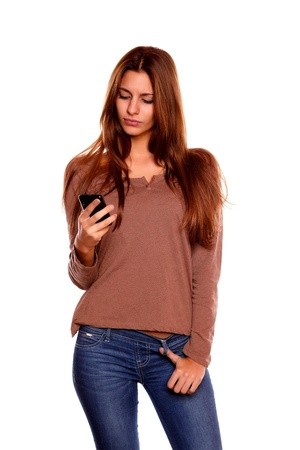 Portrait of a young woman with long brown hair sending a message with her cellphone against white background Stock Photo - 17341922