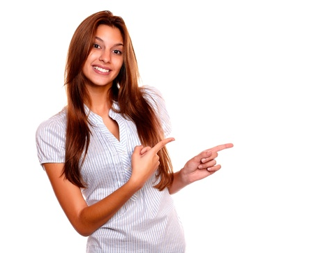 Portrait of a smiling young woman with long brown hair pointing to her left while is looking at you on isolated background - copyspace Stock Photo