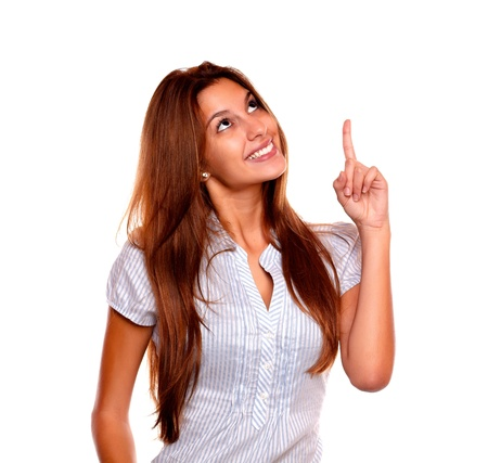 Portrait of a smiling young woman with long brown hair looking and pointing up on isolated background - copyspace Stock Photo - 17341935