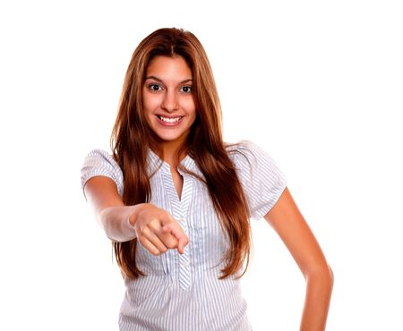 Portrait of a smiling young woman with long brown hair looking and pointing at you against white background Stock Photo - 17341939