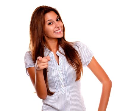 Portrait of a smiling young female with long brown hair looking and pointing at you against white background Stock Photo - 17341942