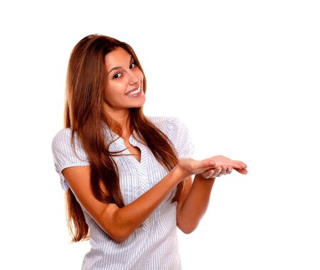Portrait of a charming smiling young woman with long brown hair holding out her palms looking at you and showing you copyspace on white background Stock Photo - 17341967