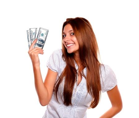 gotówka: Portret szczęśliwa mÅ'oda kobieta trzyma siÄ™ gotówki natomiast patrzy na ciebie na tle izolowane Zdjęcie Seryjne