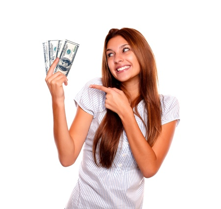 Portrait of a smiling young woman with long brown hair looking and pointing to cash money on isolated background Stock Photo