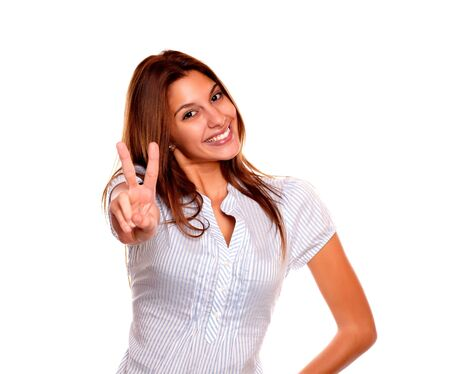 Portrait of a young woman with long hair smiling and showing you victory sign on white background Stock Photo - 17341958