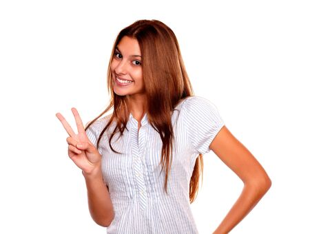 Portrait of a young female with long hair smiling and showing you victory sign on white background Stock Photo - 17341945