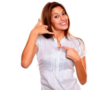 Portrait of a smiling young woman pointing and saying at you call me against white background photo