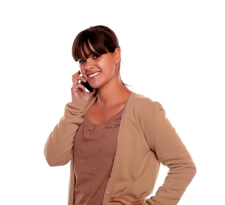conversing: Portrait of a smiling young female conversing on cellphone against white background