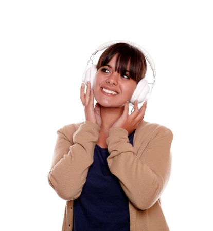 Portrait of a relaxed young woman with headphone listening music and looking to her right up against white background - copyspace Stock Photo - 17542533