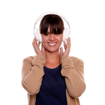 Portrait of a charming young woman with headphone listening music and looking at you against white background Stock Photo - 17542492
