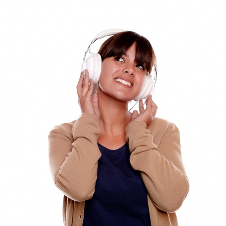 Portrait of a smiling young woman with headphone listening music and looking to her right up against white background - copyspace Stock Photo - 17542482