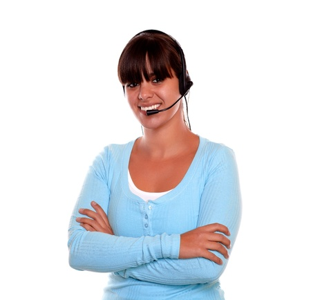 Portrait of a pretty call center employee smiling at you while wearing her headphones on isolated background photo
