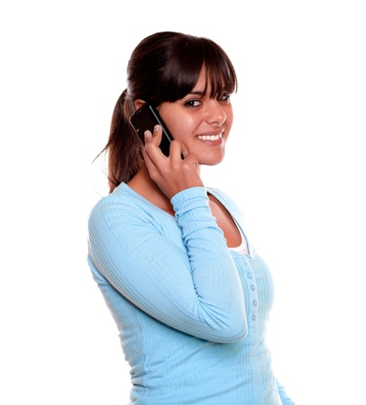 Portrait of a smiling young woman with fringes speaking on cellphone while is looking at you on isolated background photo