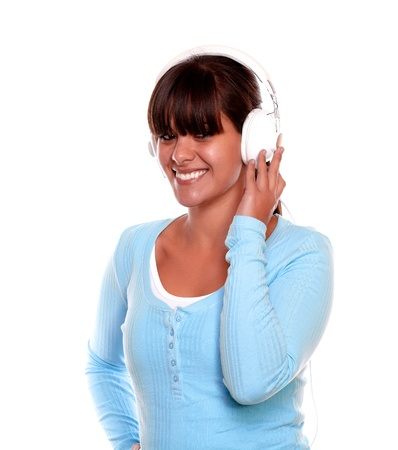 Portrait of a smiling young woman with headphone listening to music on blue t-shirt against white background photo
