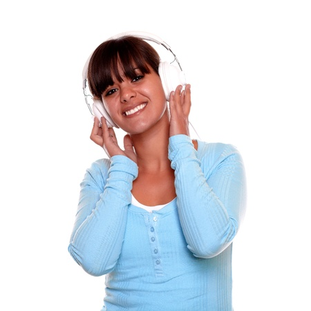 Portrait of a happy young woman with headphone listening to music on blue t-shirt while is looking at you on isolated background photo