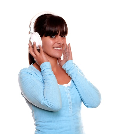 Portrait of a charming young woman with headphone listening to music on blue t-shirt while is looking at you on isolated background photo