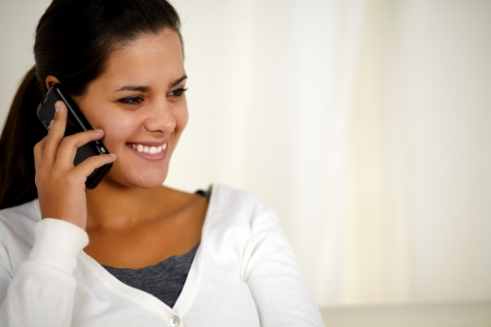 Portrait of a charming young woman conversing on mobile phone