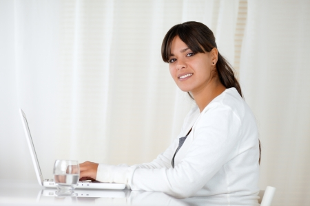 Portrait of a charming young woman looking at you while is working on laptop - copyspace photo