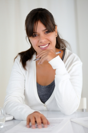 Portrait of a working young woman looking and smiling at you photo