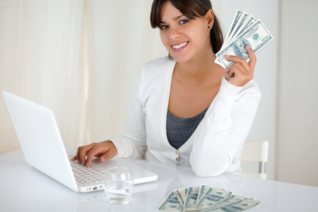Portrait of a smiling young woman holding up cash money in front of her laptop while is looking at you