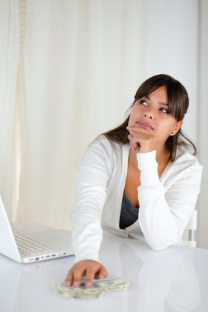 Portrait of a young woman thinking with cash money and her laptop computer photo