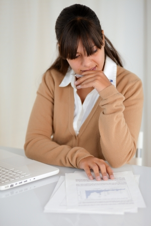 Portrait of a pensive charming young woman reading documents in front of her laptop computer