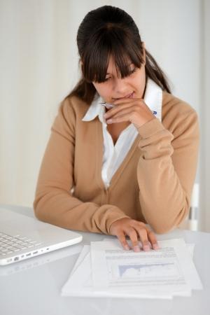 Portret van een peinzende charmante jonge vrouw lezen van documenten in de voorkant van haar laptop computer Stockfoto