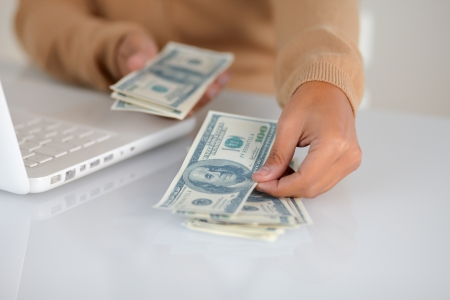 Portrait of a young woman counting cash dollars for buying in front of her laptop photo