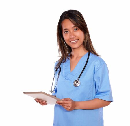 Portrait of a charming asiatic nurse woman looking at you using her tablet pc on blue uniform against white background Stock Photo - 19848977
