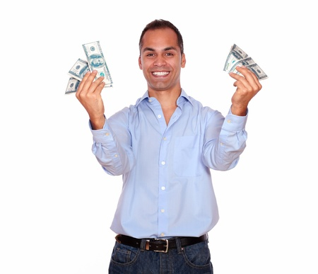 Portrait of an excited adult man looking at you and holding cash money against white background