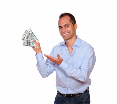 Portrait of a smiling latin adult man looking at you and holding cash dollars on isolated background 스톡 사진